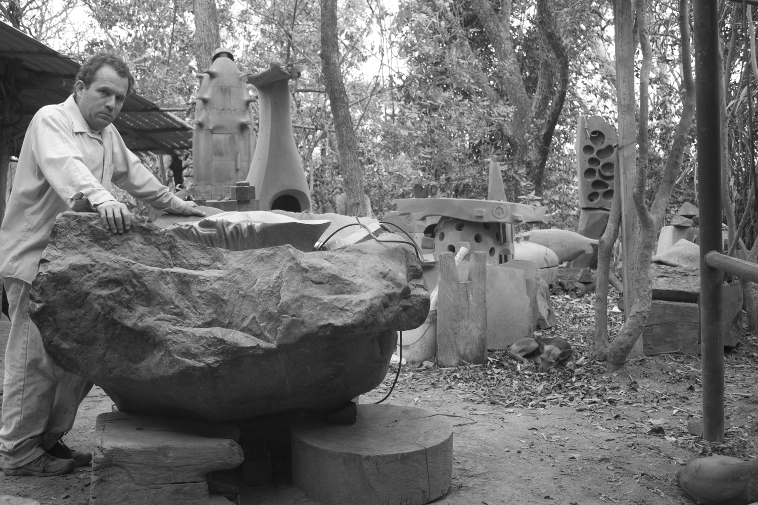 JULIO MARTINEZ BARNETCHE in the outdoor section of his 'jungle' workshop. With finished and semi-finished sculptures and stones ready to be carved into sculptures.