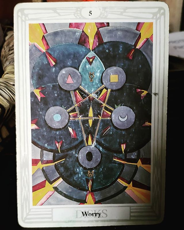 """The Five of Disks  All but one of the Fives in Thoth Tarot depict an inverted pentagram, which represents the dominion of the material elements over the spirit; it is considered the """"bad"""" pentagram. """"It isn't bad, exactly, but it is outside the natural order of things.  When fives turn up in readings we often feel as if that realm of our lives is """"upside-down"""". In this case it is the realm of earth, of money, health, and all the other material things that allow our meat bag bodies to survive, so that our spirits can exist on this plane. The title of the card is Worry, and that is usually a very good literal meaning for it. But it goes deeper, because this is the tarot, it always goes deeper.  The material world is often neglected by spiritual types. We are concerned with the big questions, the whys of existence, and divine eternity, who has time to care about something as vulgar and trivial as money? But I'd like to ask that question a different way. Who has time to devote to their spiritual development when they don't know where their next meal is coming from? Or the next meal for their children? There are a few truly extraordinary souls in this world who really can release all attachment to the material in order to attain spiritual ascension. They are beggars, perennial travelers, and monks. They are not like most people; not like me, and probably not like you, who are reading an Instagram post on a device likely worth almost a thousand dollars.  So for us, it is really a question of balance. If we care a bit about our material support systems all the time we can avoid paralyzing stress when those neglected systems collapse. The converse of this is obviously caring too much, but if you remember that money is here to serve you, you are not here to serve money, you can keep the pentagram of your finances upright.  This card doesn't have that much of a positive/negative meaning split, but I've included an aspect that is affected by air energy in the comments."""