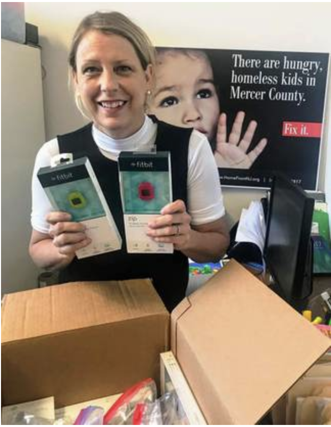 Liza Peck, support services liaison for HomeFront Family Campus, opens a box of new and refurbished trackers.