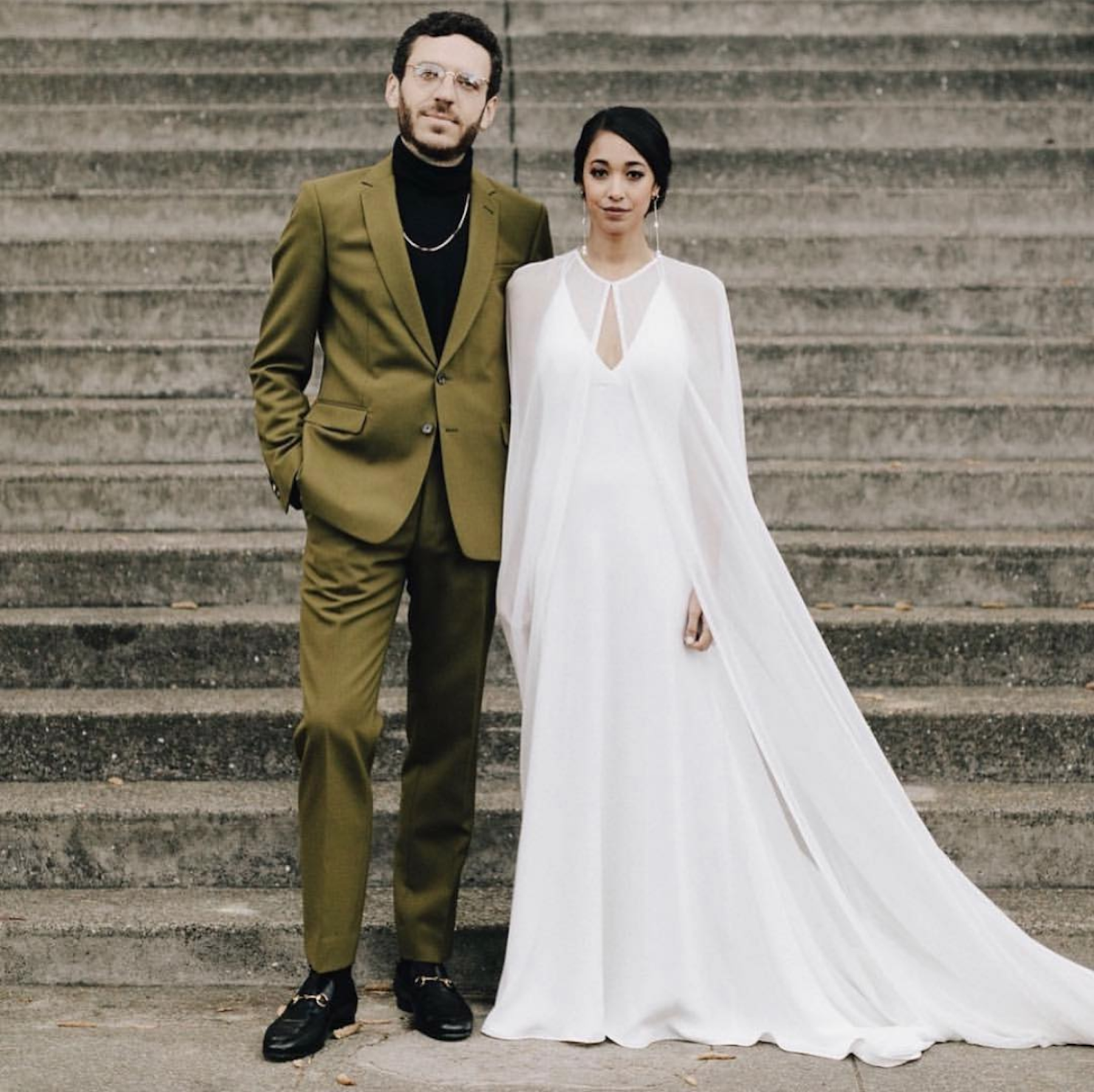 This beautiful bride was simply elegant in Odylyne the Ceremony. - It's safe to say that capes continue to have their moment. We love her groom's super fly green suit!Photo by James Moes.