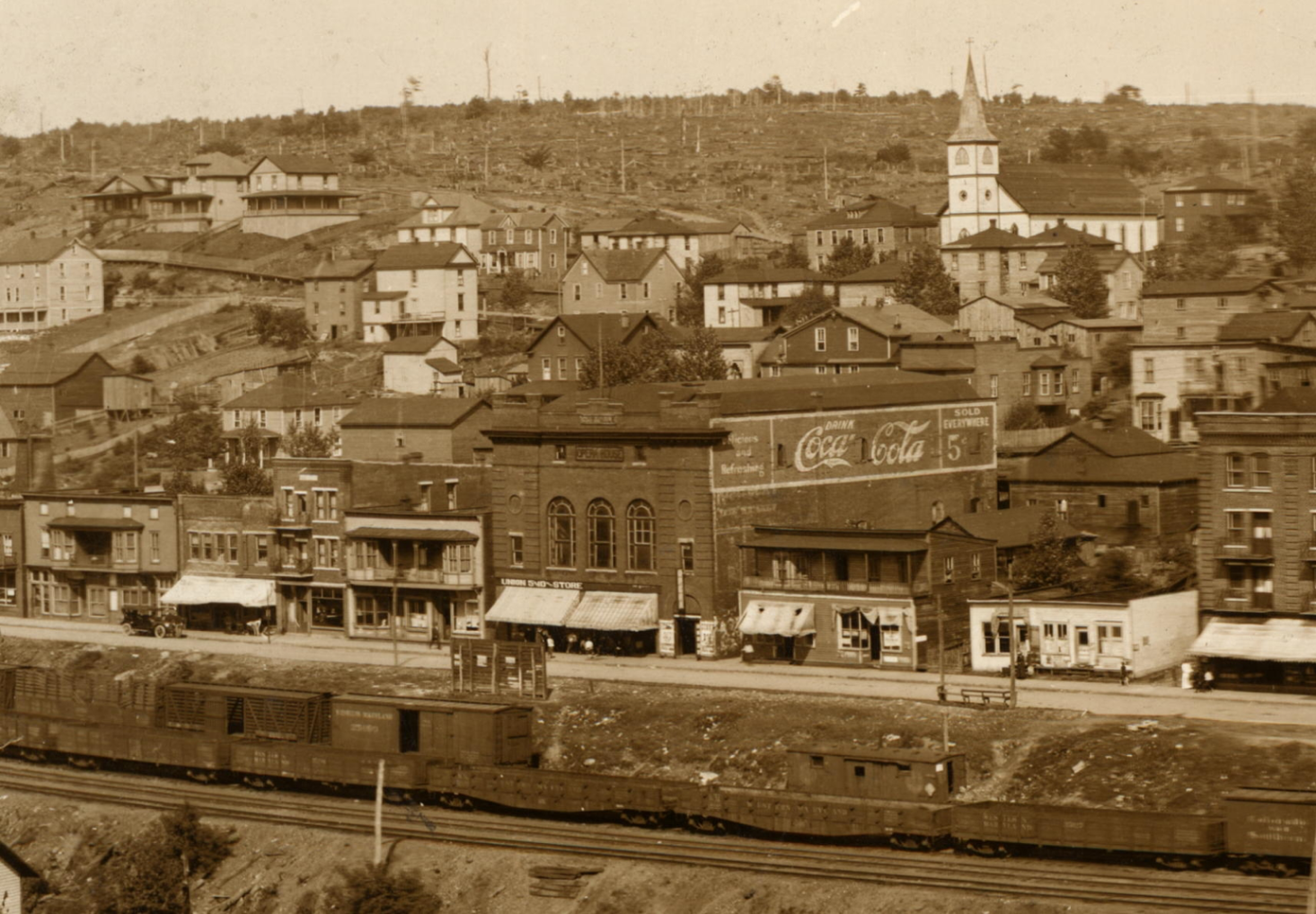 Front Street in Thomas, ca. 1914. Note the clear-cut hillside behind Thomas and the rail line on the riverfront. This photo was taken just before Hiram Cottrill sold the building to the Sutton family (see below).
