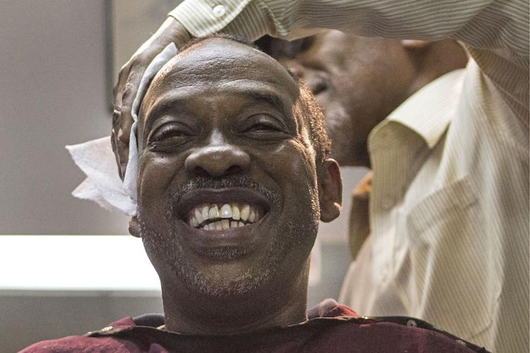 Vincent Tate, 51, receives a haircut Tuesday from Edward Young, 64, at the Clean Cut Barber Shop on Northwest Fifth Avenue. Tate moved from Alabama to Gainesville for a fresh start, and he has worked for the Alachua County School Board for 25 years.  Samuel Thomas / Alligator Staff