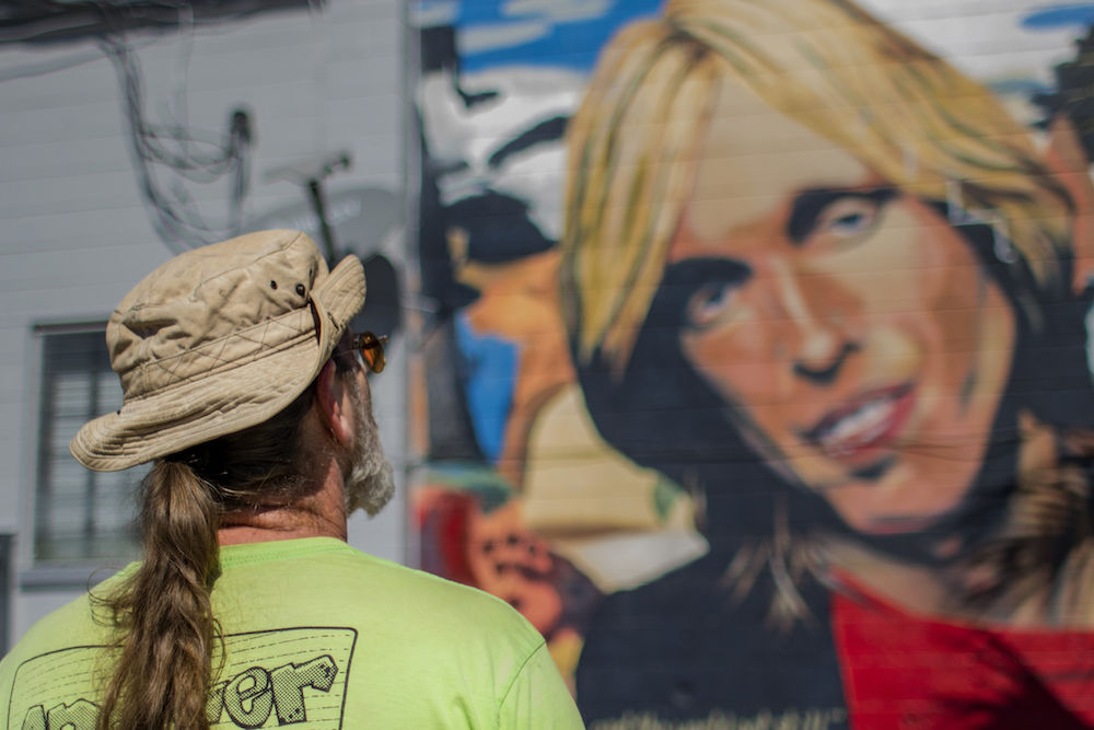 Blake Harrison looks at his mural of Tom Petty on the corner of Southeast 16th Avenue and South Main Street.  Aaron Ritter / Alligator Staff