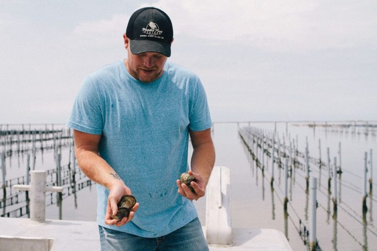 Lane Zirlott holding Murder Point Oysters