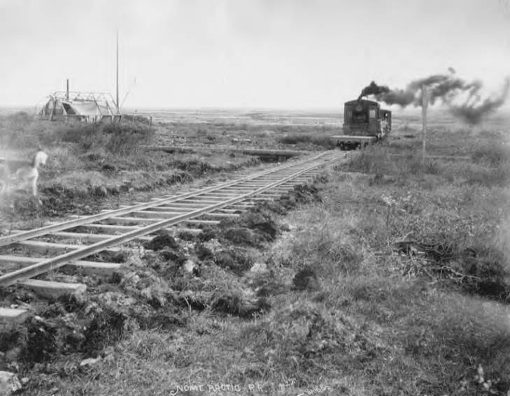 Nome Arctic Railroad train approaching through field with dogs and building framework nearby, vicinity of Nome, 1907.jpg