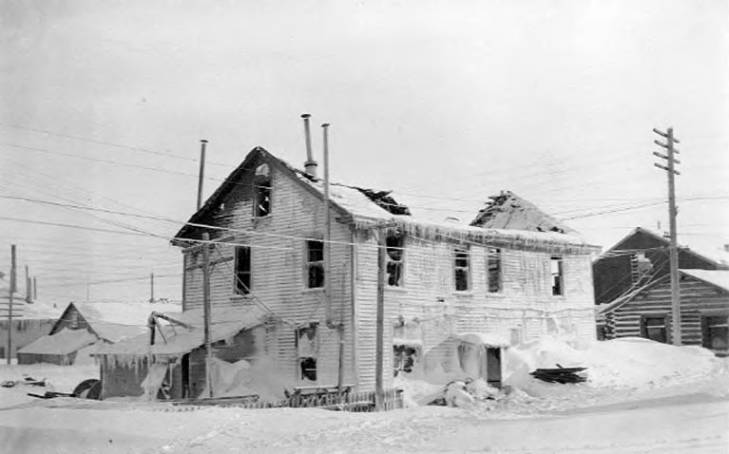Burned-out shell of large building with collapsed roof and covered with icicles and snow, Nome, Alaska, between 1905 and 1915.jpg