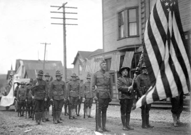Army soldiers on parade in street holding flags, Nome, Alaska, between 1913 and 1923.jpg