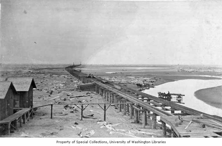 Construction of long railroad trestle, with horse-drawn carts and driftwood visible beyond tracks, Nome.jpg
