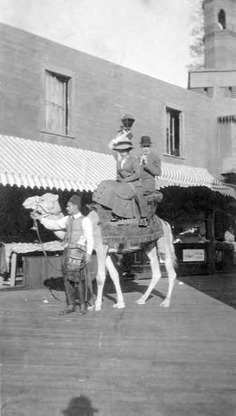 Couple (including Ralph Lomen riding camel down plank-lined city street with awnings, Nome, circa 1900-1920.jpg