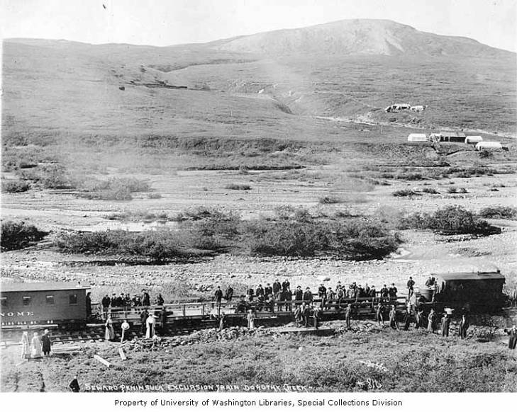 Excursion train and people standing on the flatbed cars, Dorothy Creek, Seward Peninsula, Alaska, circa 1906.jpg