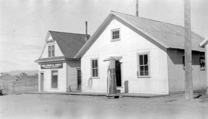 Exterior view of Lomen Commercial Company building with gas pump in front and adjacent building with sign reading Lomen Commercial Company Freight Office, Nome, 1925-1940.jpg