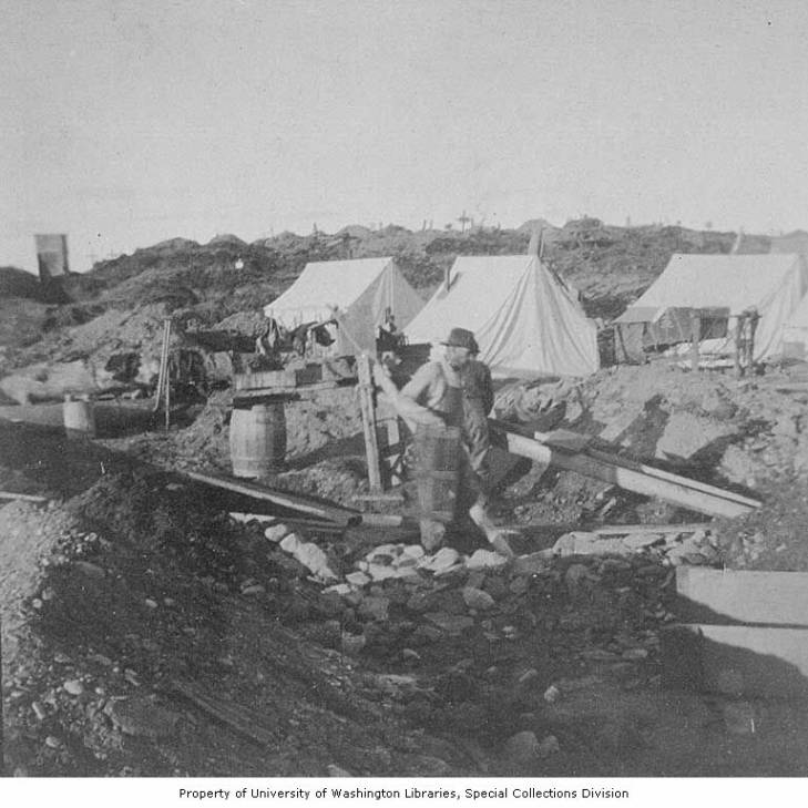 Gold miners working a sluicing operation, with tents and a cemetery in the background, Nome, Alaska, circa 1900.jpg