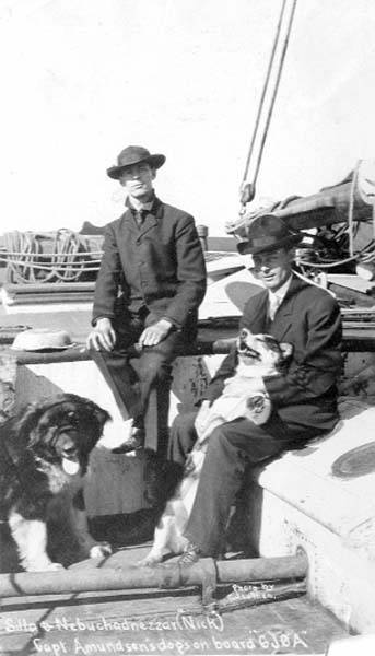 Harry and George Lomen with Lomens' dog Silla and Roald Amundsen's dog Nebuchadnezzar (Nick) on board ship Gjoa, Nome, September 1906.jpg