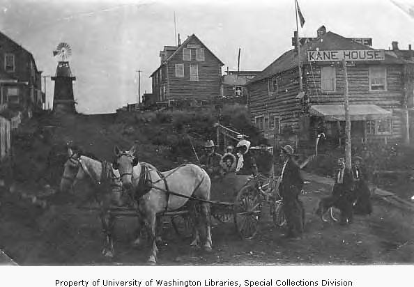 Horse-drawn carriage with five passengers in front of Kane House, Council City, Alaska.jpg