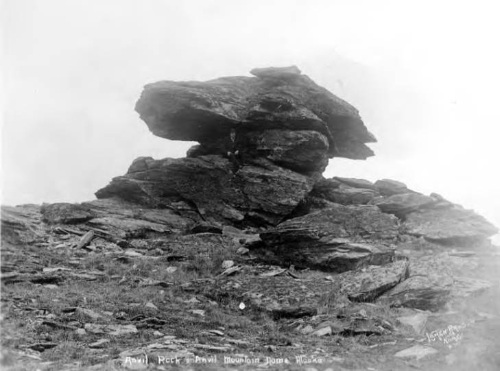 Man sitting on Anvil Rock on Anvil Mountain, vicinity of Nome, circa 1915.jpg