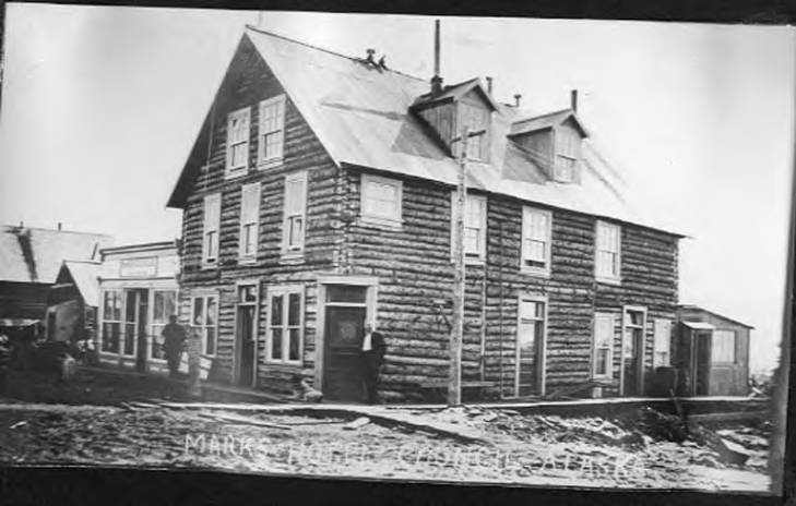 Man standing outside of Marks Hotel, Council, Alaska, circa 1906.jpg
