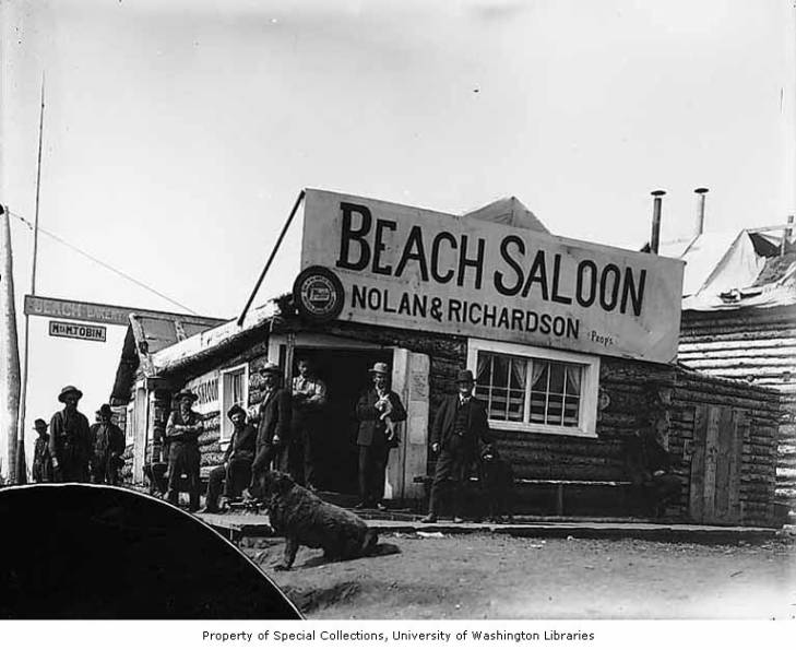 Men and dogs in front of the Beach Saloon and Bakery, Council, Alaska, circa 1907.jpg
