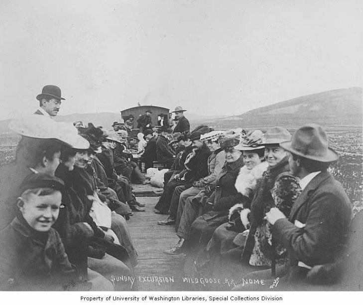 Men, women and children sitting in an open rail car, Wild Goose Railroad, Nome, Alaska, circa 1906.jpg