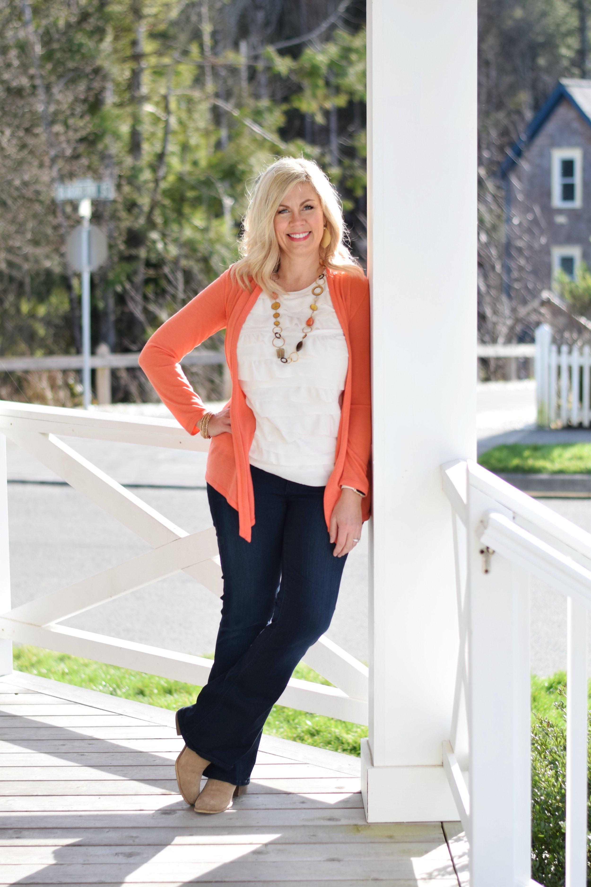 blonde woman wearing orange sweater leaning against post susie lane.jpg