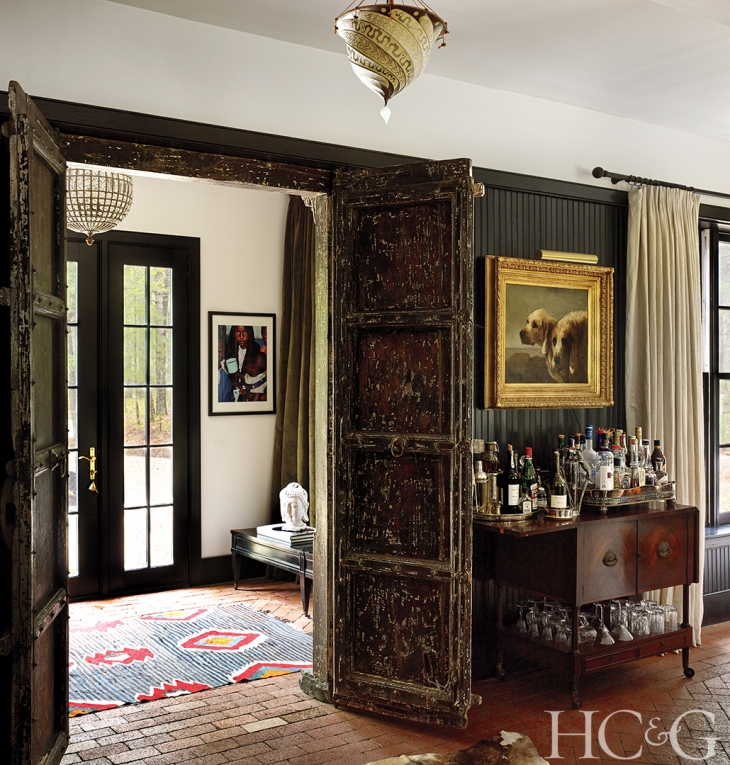 Decorative Indian mahogany doors from the late 1800s beckon in the entryway; the bar dates from the 1930s.