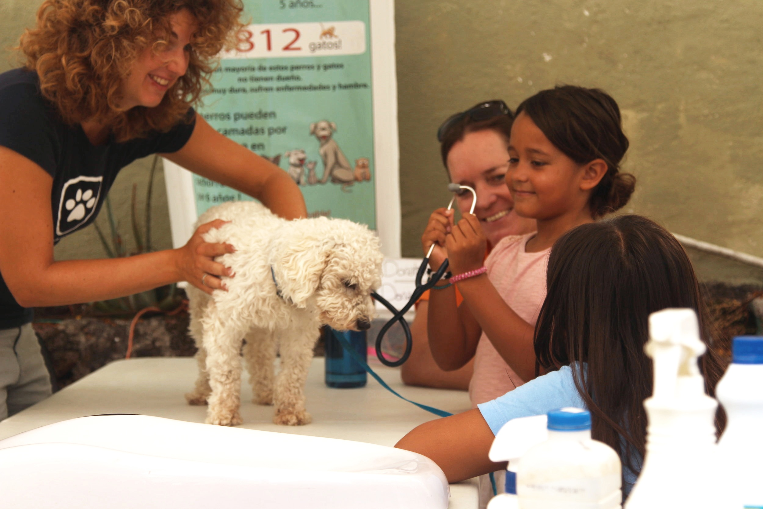 Figura 2 . La Dra. Carmen Barba Claassens enseña a jóvenes galapagueños como oír los latidos del corazón de su perro. Foto: Darwin Animal Doctors