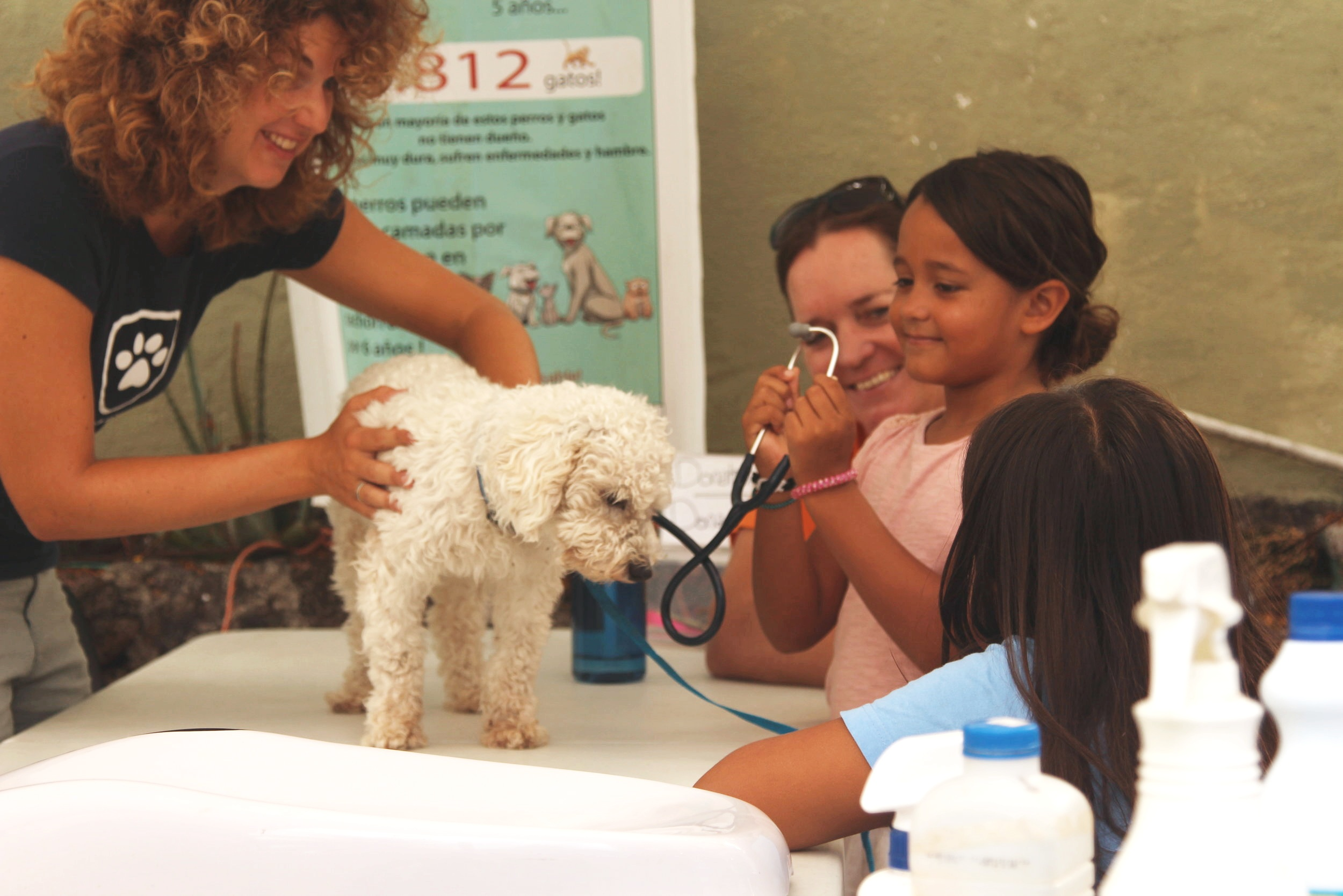 Figure 2.  Dr. Carmen Barba Claassens shows young Galapagueñas how to listen to their dog's heartbeat. Photo: Darwin Animal Doctors