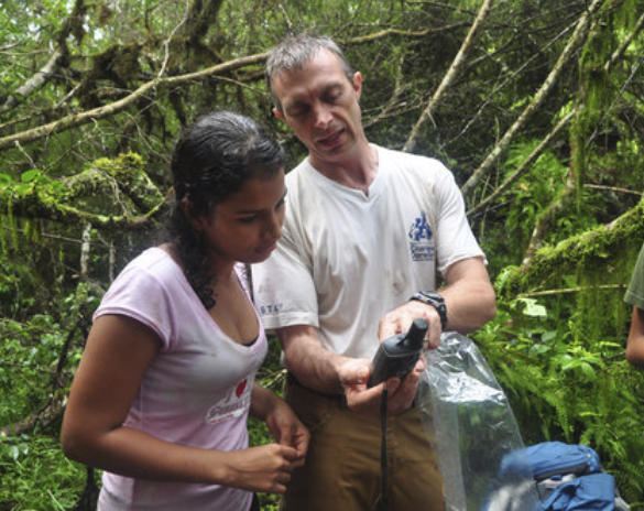 Figure 4.  Dr. Steve Blake teaches a student how to record the location where a scat sample was found, for future analysis. Photo: EPI Archive