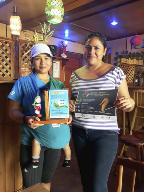 Figure 6.  Daniela Chalén with her son and one of San Cristobal's leaders in the plastic reduction campaign, in her place of business. Photo: Ashleigh Klingman