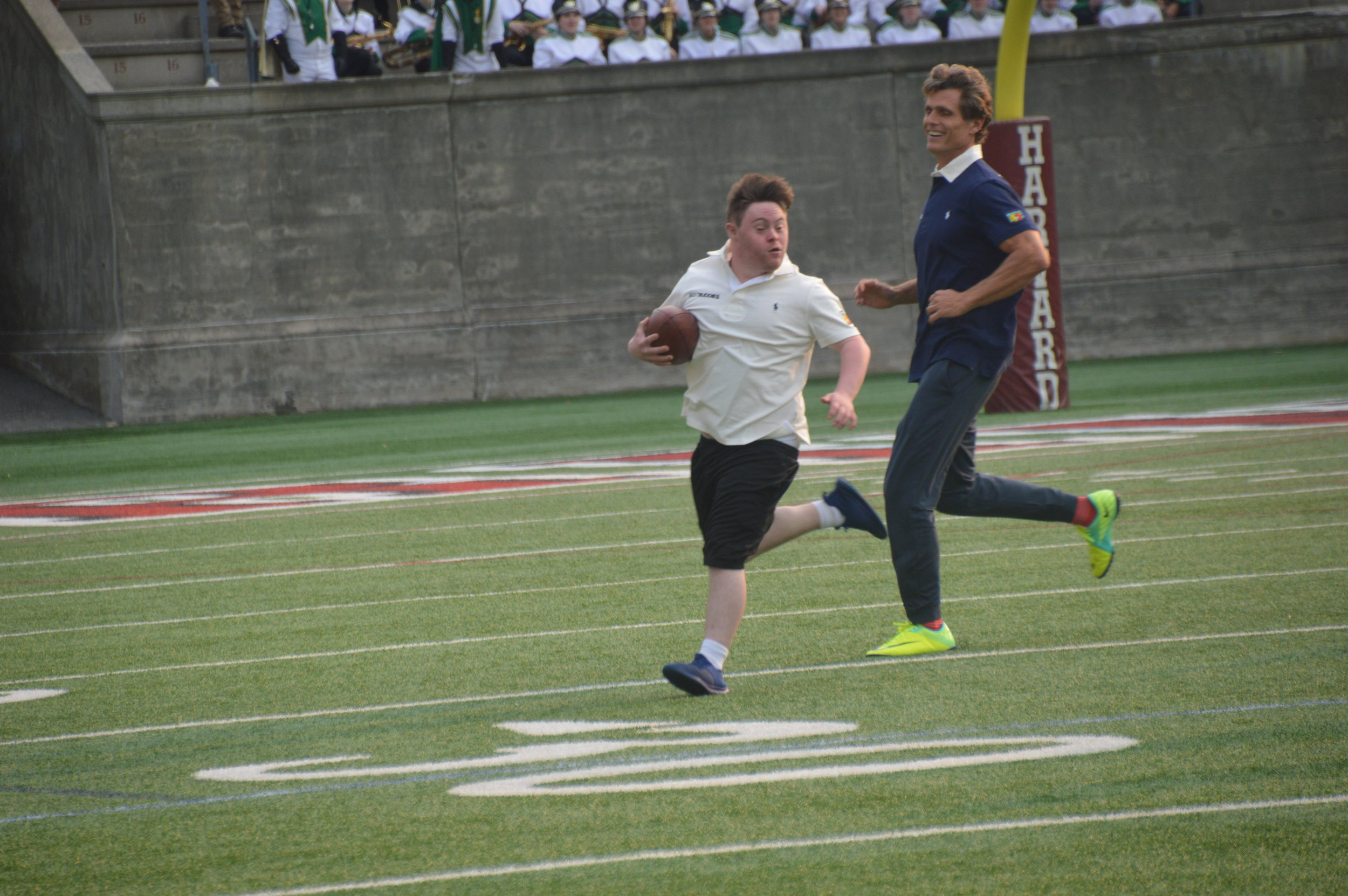 Anthony Kennedy Shriver chases after an athlete during the 20th Annual Tom Brady Best Buddies Football Challenge.