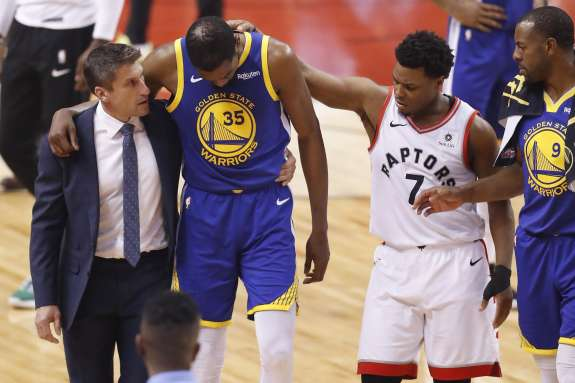 Warriors Kevin Durant and Raptors Kyle Lowry after Durant went down with a leg injury in game 5