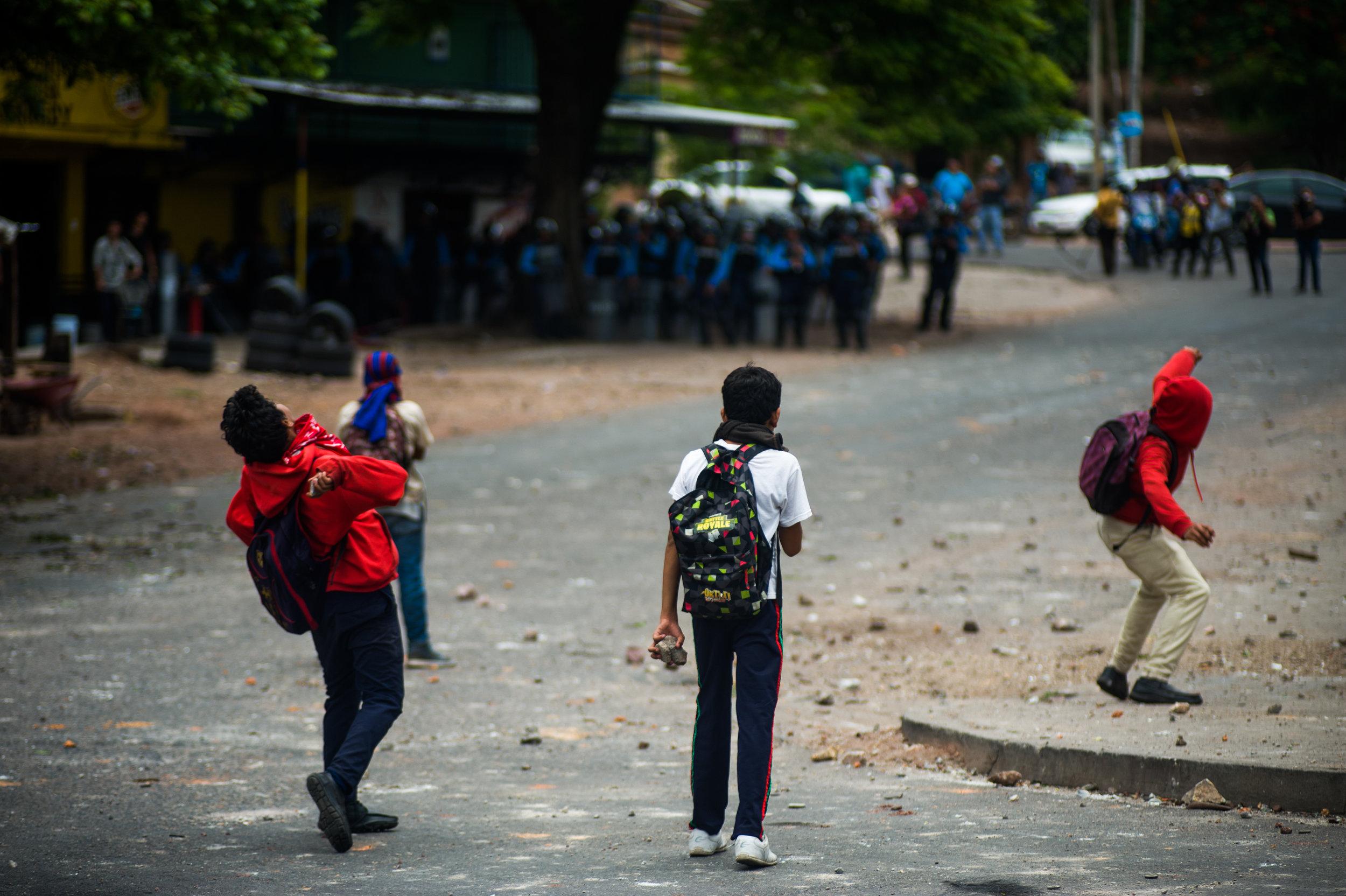 Adolescentes y jóvenes se defienden de la Policía Nacional y el Ejercito de Honduras que utiliza gas lacrimogeno y balas de goma contra los estudiantes. Foto: Camilo Freedman/La Crónica