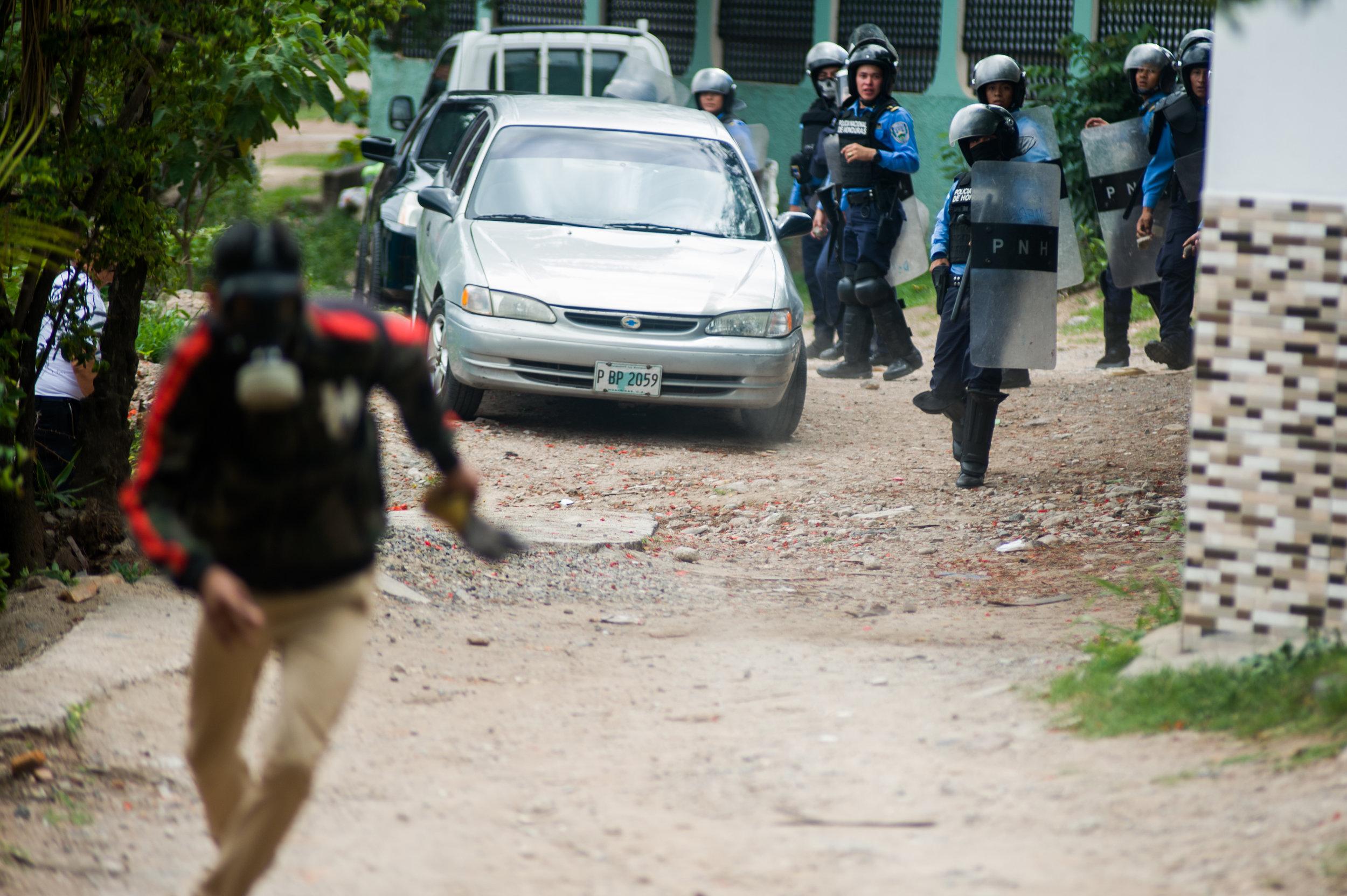 Un miembro de la Policia Nacional toma su arma con el fin de amenazar a estudiantes y miembros de la prensa en una protesta en Tegucigalpa. Foto: Camilo Freedman/La Crónica