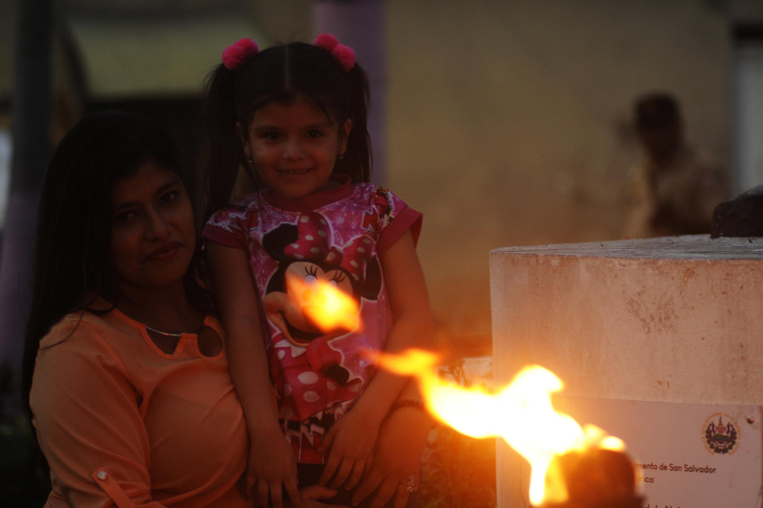 """Una mujer y su hija observan una """"bola de fuego"""", que arde en llamas frente a la iglesia de Nejapa. Foto: Camilo Freedman"""