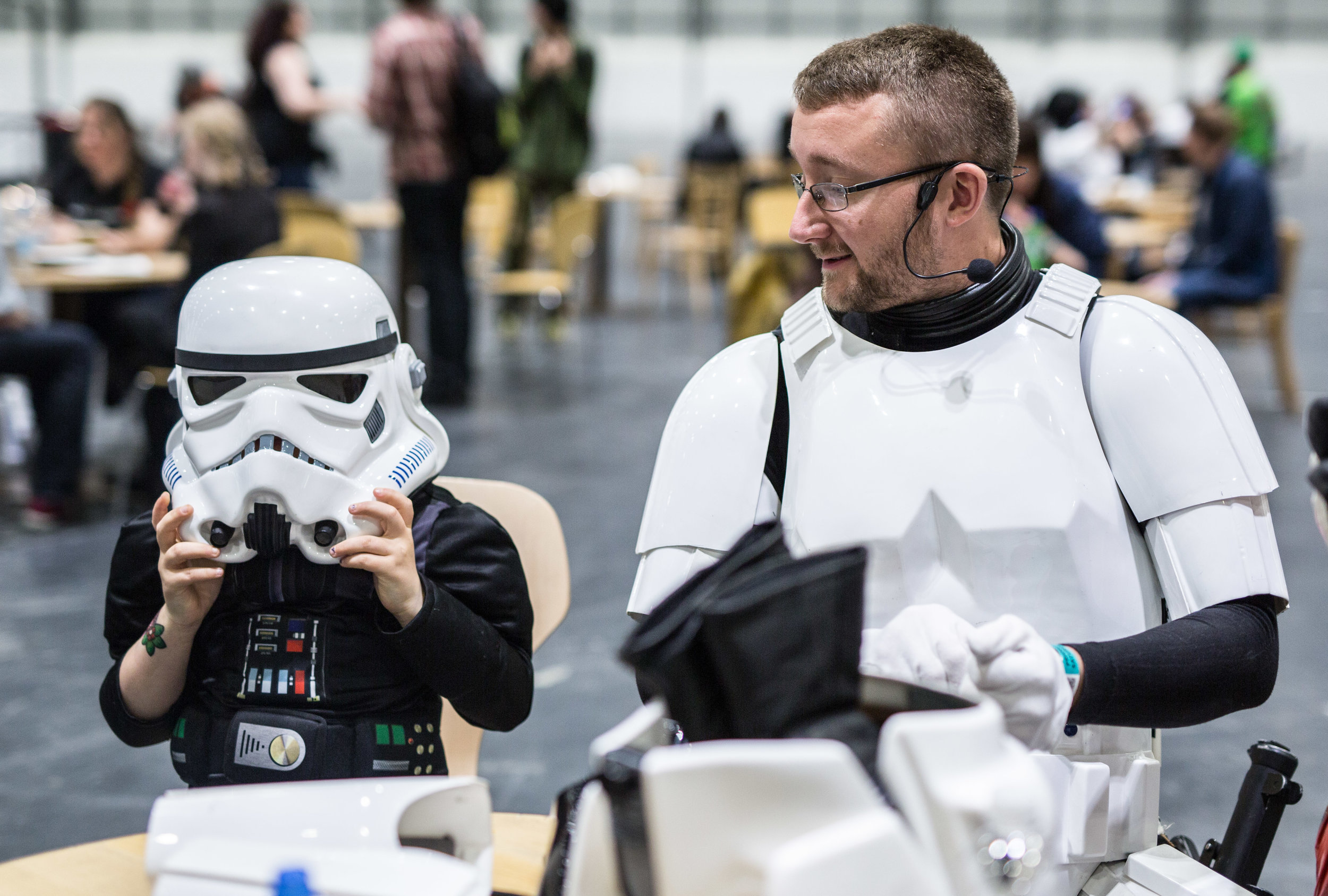 A child in a Darth Vader (Star Wars) outfit tries on a Storm Trooper helmet at the MCM EXPO London Comic Con which is being held at the ExCel Centre between 22-24th May 2015