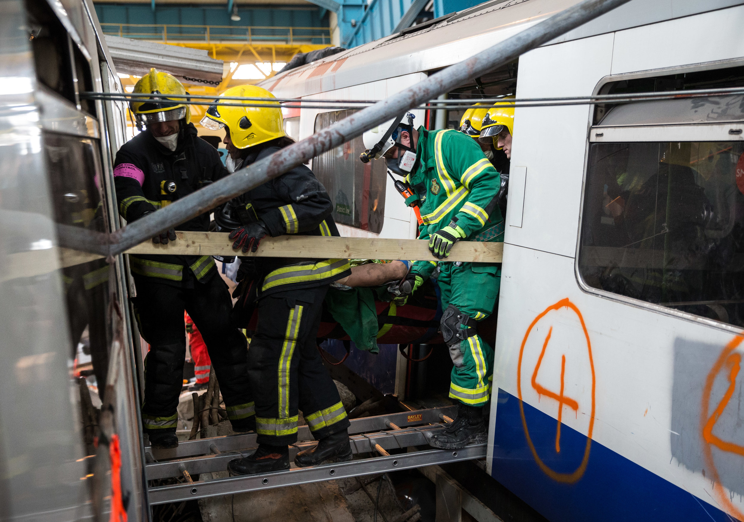Emergency service workers move a 'survivor' from one destroyed train carriage to another