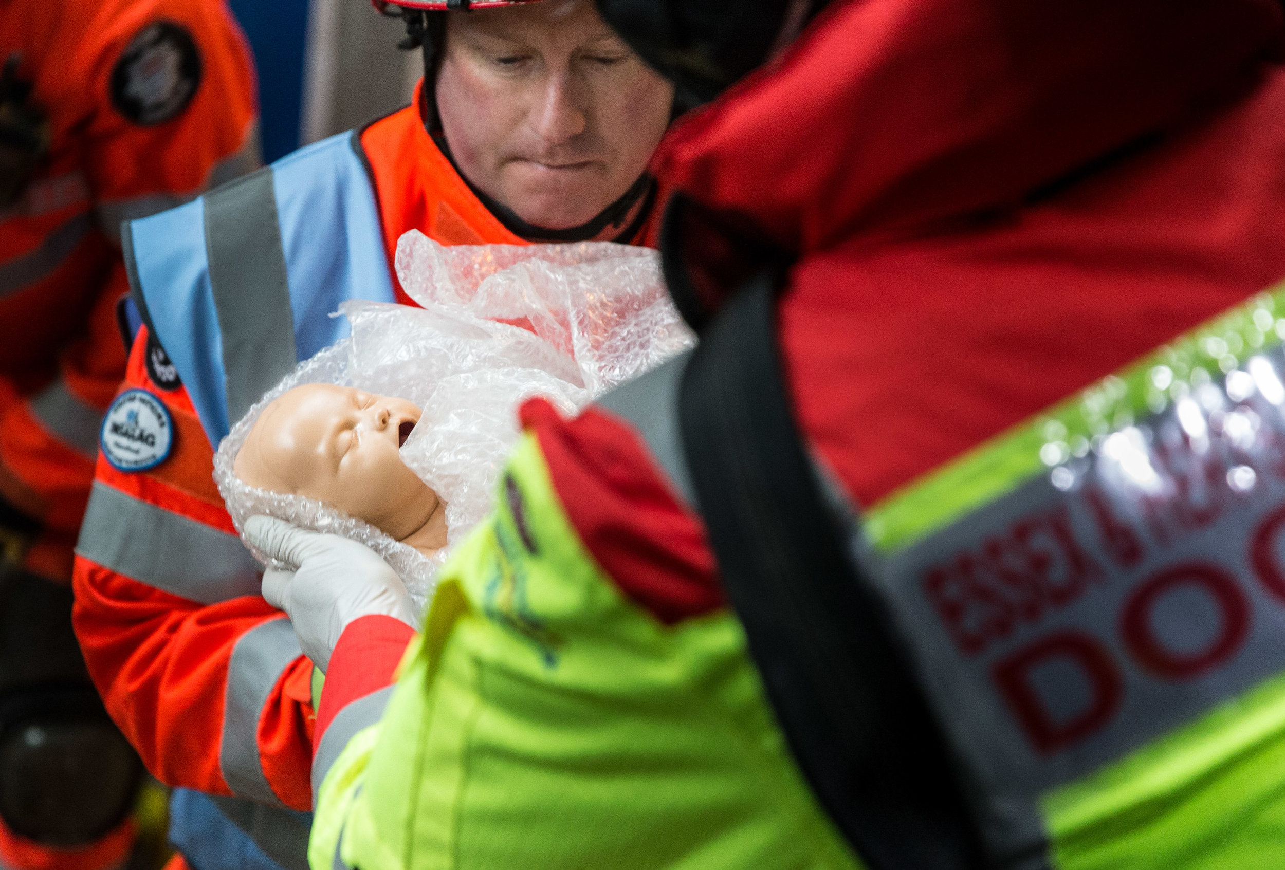 Emergency service workers handle a baby doll