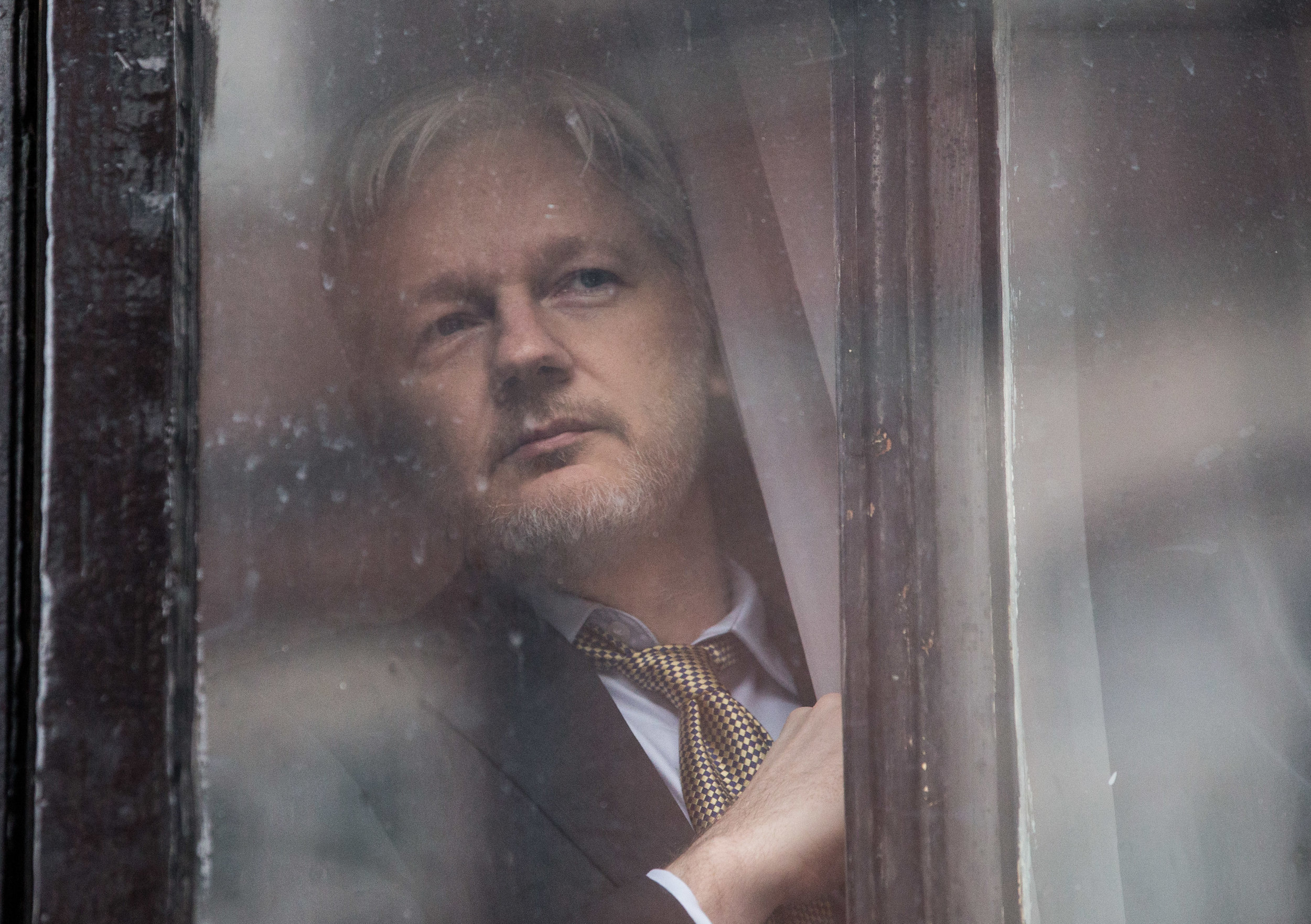 Julian Assange looking out through a door at the Embassy