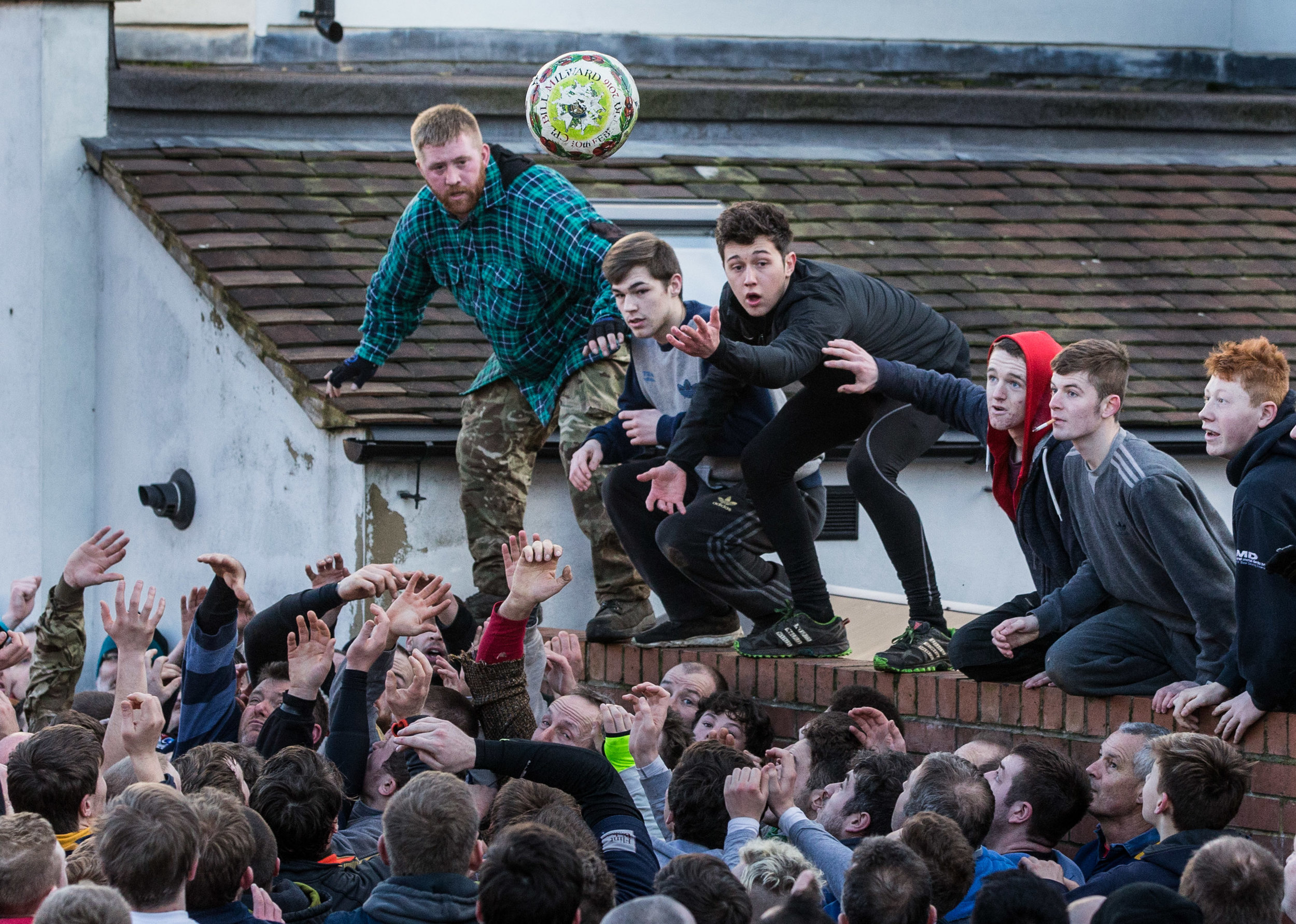 Participants watch as the ball is thrown during Shrovetide football in Ashbourne
