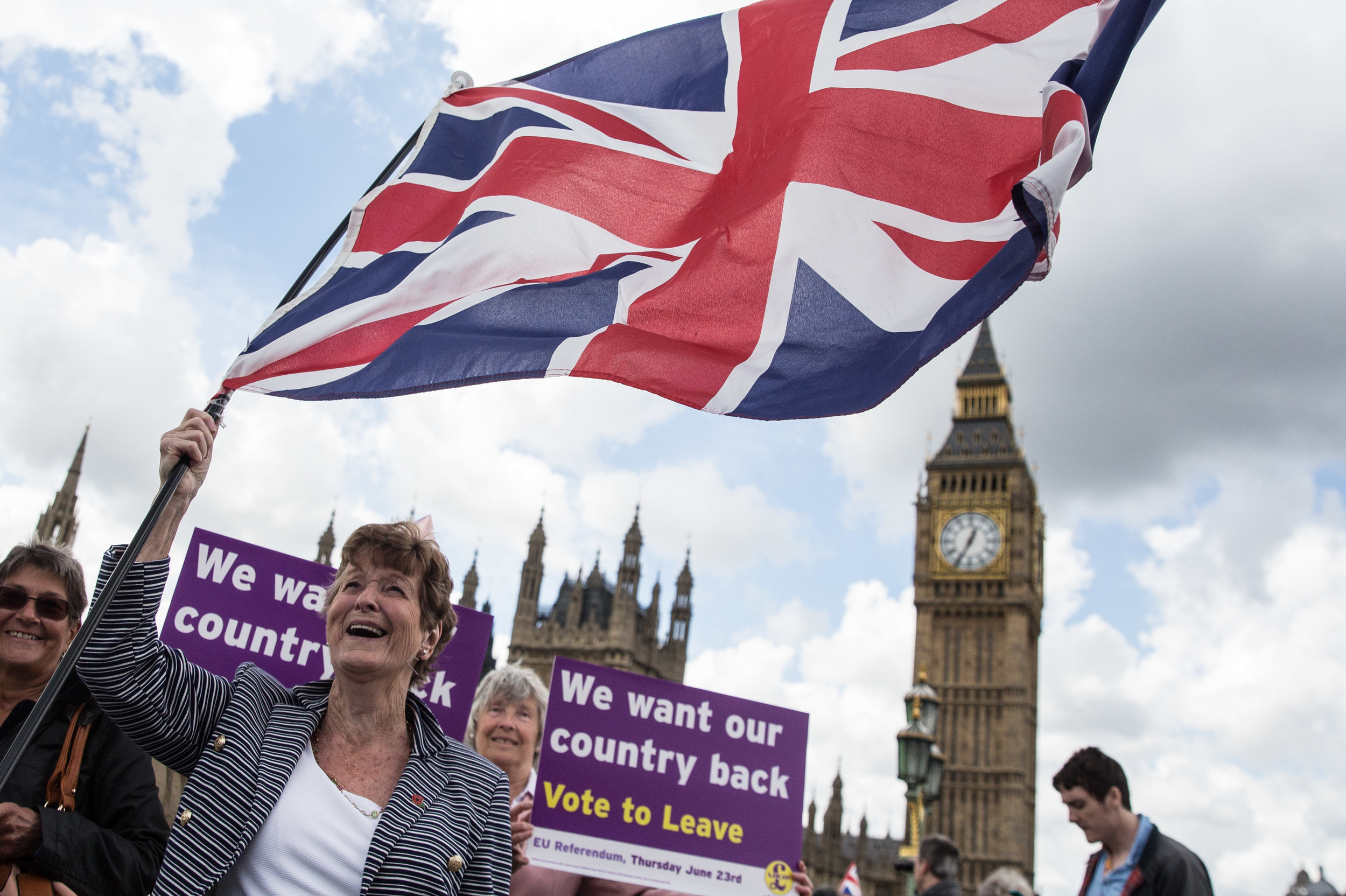 A woman holding a Union Jack flag and wearing a Union Jack hat on Westminster Bridge as a flotilla of 'Fishing for Leave' vessels which sailed from Southend to Parliament