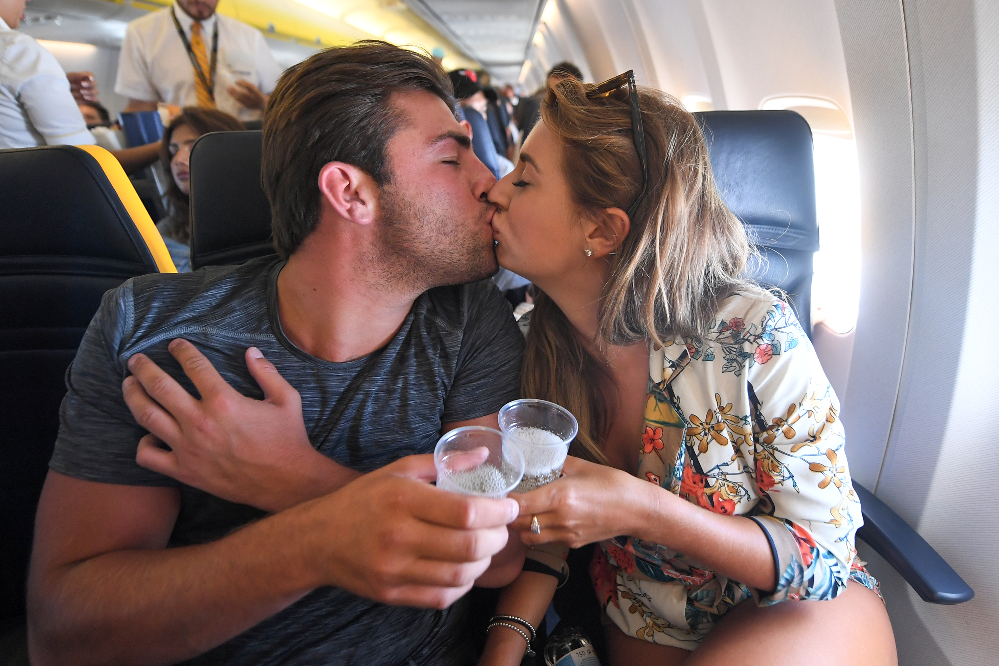 Dani Dyer and Jack Fincham with champagne on the flight from Palma de Mallorca to London
