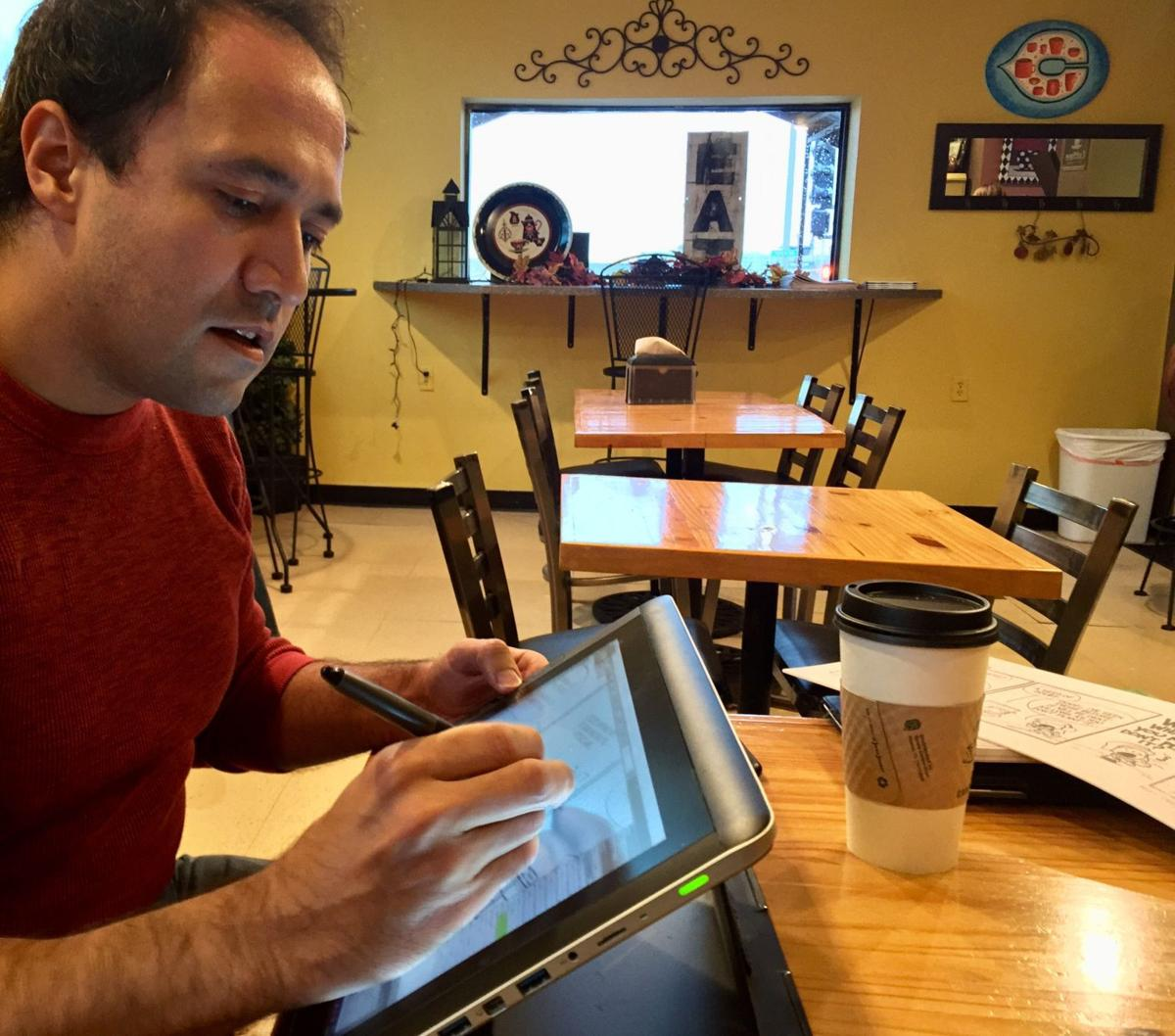 """Quad-City cartoonist Jason Platt sketches a comic strip on his Wacom tablet Monday at Java Java Cafe in Davenport. Earlier this fall, the 43-year-old father released a new book of his stories and illustrations titled, """"mister & Me: Of Castles & Kings."""""""