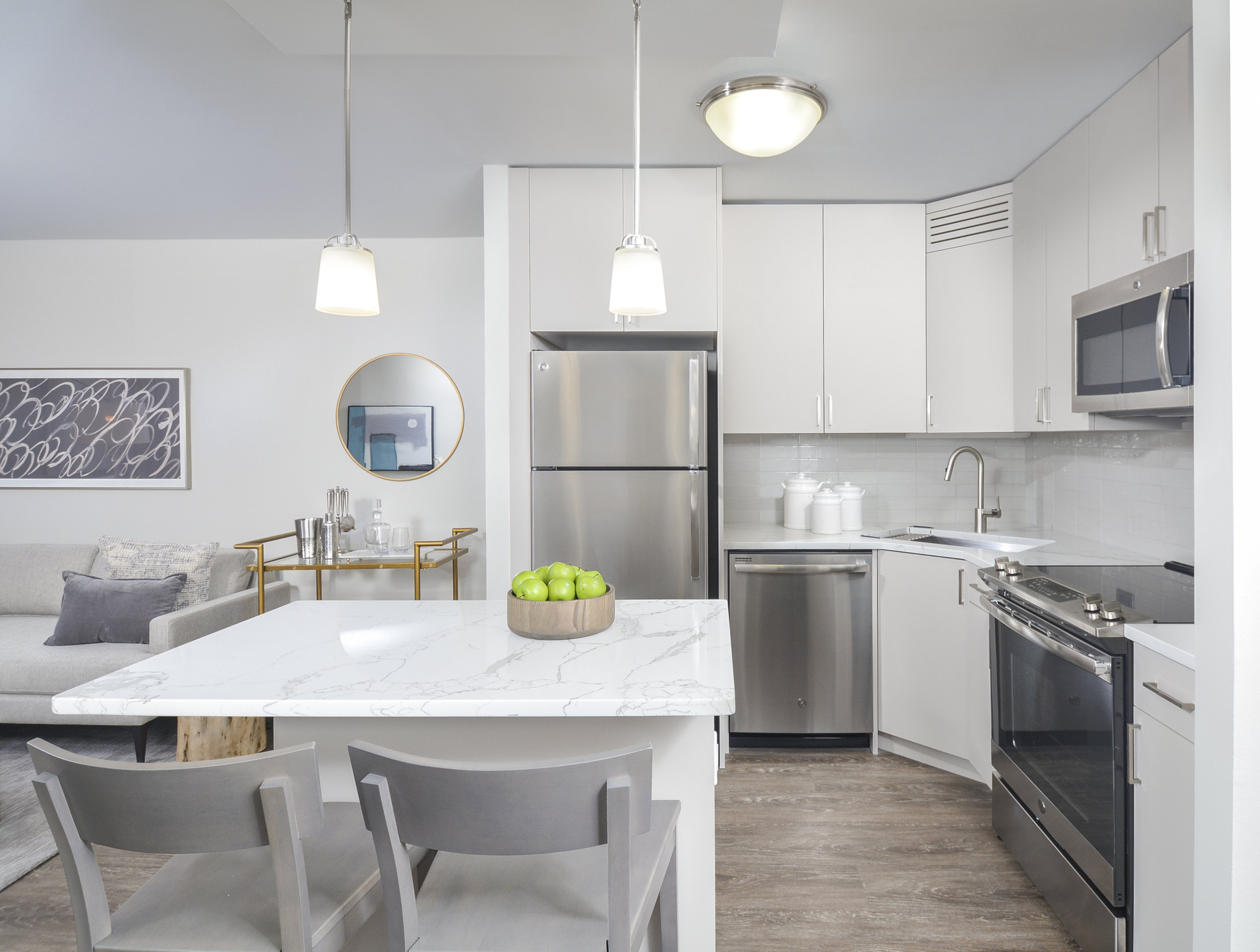 A cool grey backsplash and warm cabinets allows for the kitchen to feel like a natural part of the space.