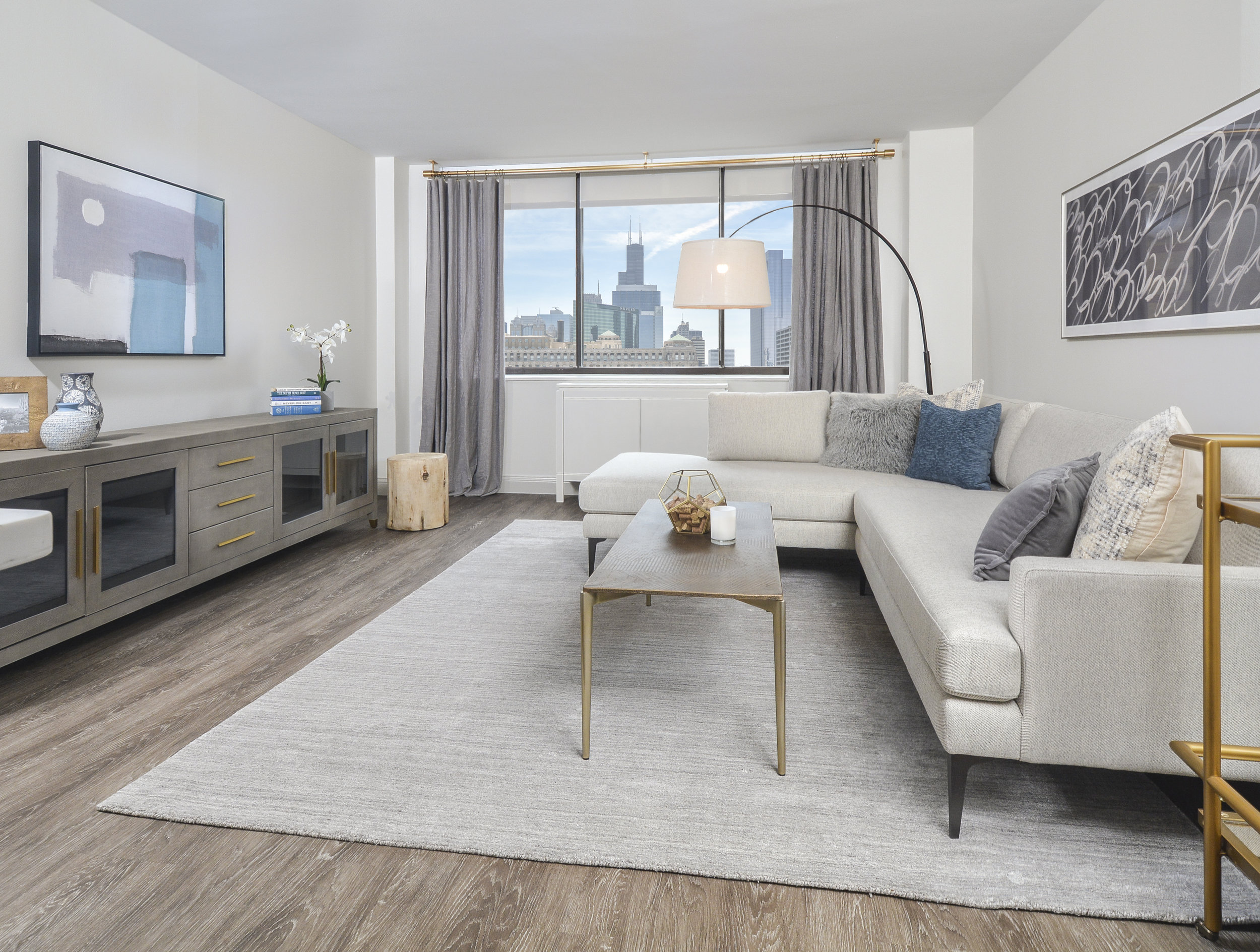 Brass finishes and pops of blue liven up the living room and pairs marvelously with breathtaking Chicago skyline.