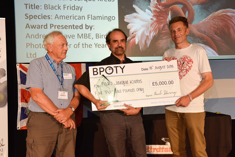 The 2018 Bird Photographer of the Year winner, Pedro Jarque Krebs from Peru (centre) receives his award from BPOTY director Andrew Cleave MBE (left) and BPOTY head judge Chris Packham. Photo ©Rob Read