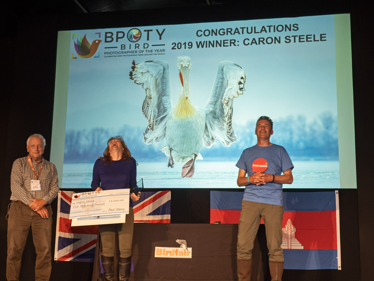 Bird Photographer of the Year winner Caron Steele from the UK collecting her cheque and trophy from BPOTY director Andrew Cleave (left) and Chris Packham (right)