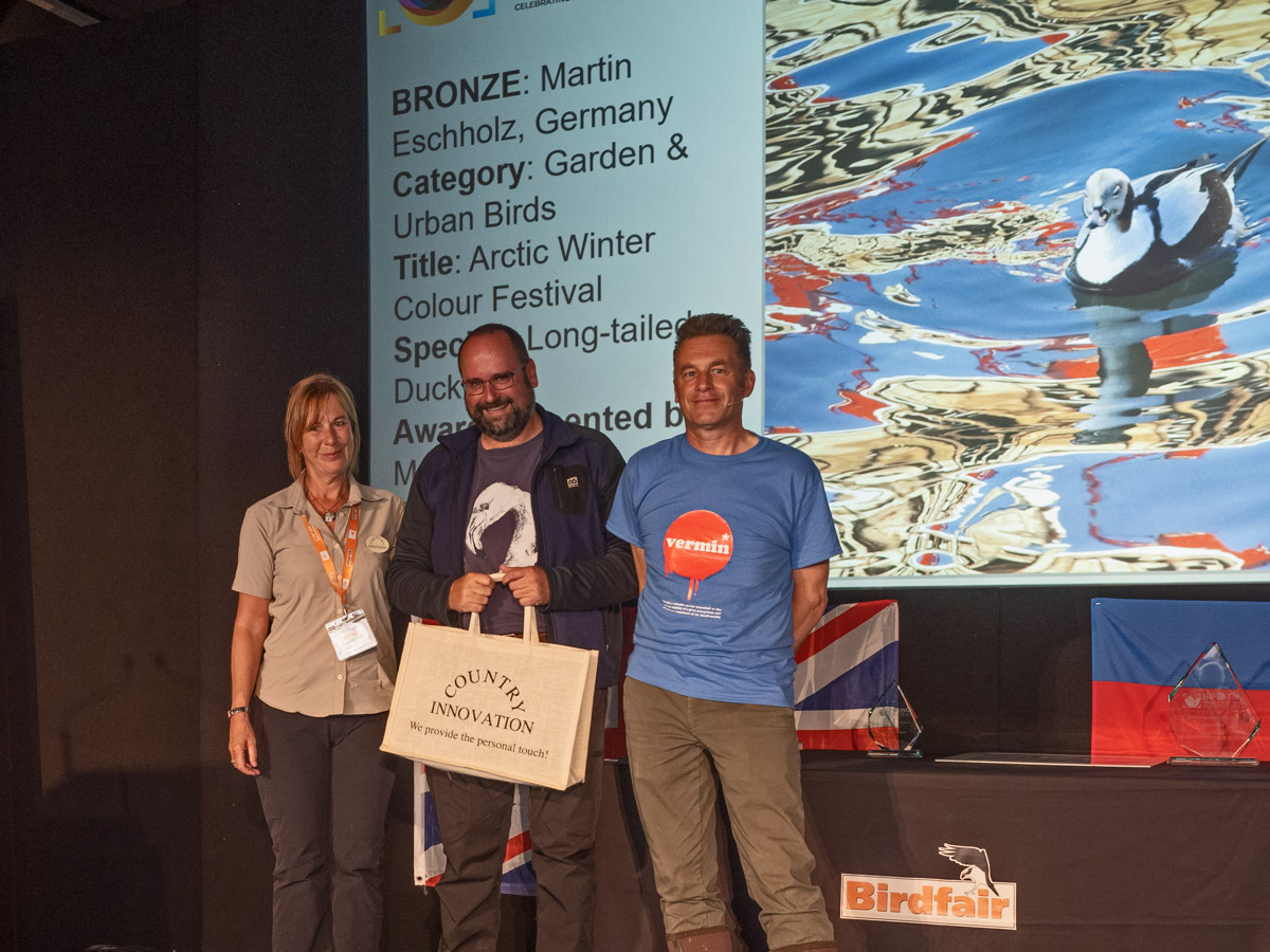 Martin Eschholtz from Germany BPOTY 2019 Garden and Urban Birds Bronze Award winner. Pictured with Maria Chilvers of Country Innovation (left) and Chris Packham (right)