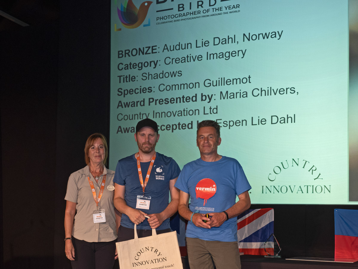 Audun Lie Dahl from Norway BPOTY 2019 Creative Imagery Bronze Award winner. Pictured are Audun's brother Espen (centre) accepting the award on his brother's behalf from Maria Chilvers (left) and Chris Packham (right)