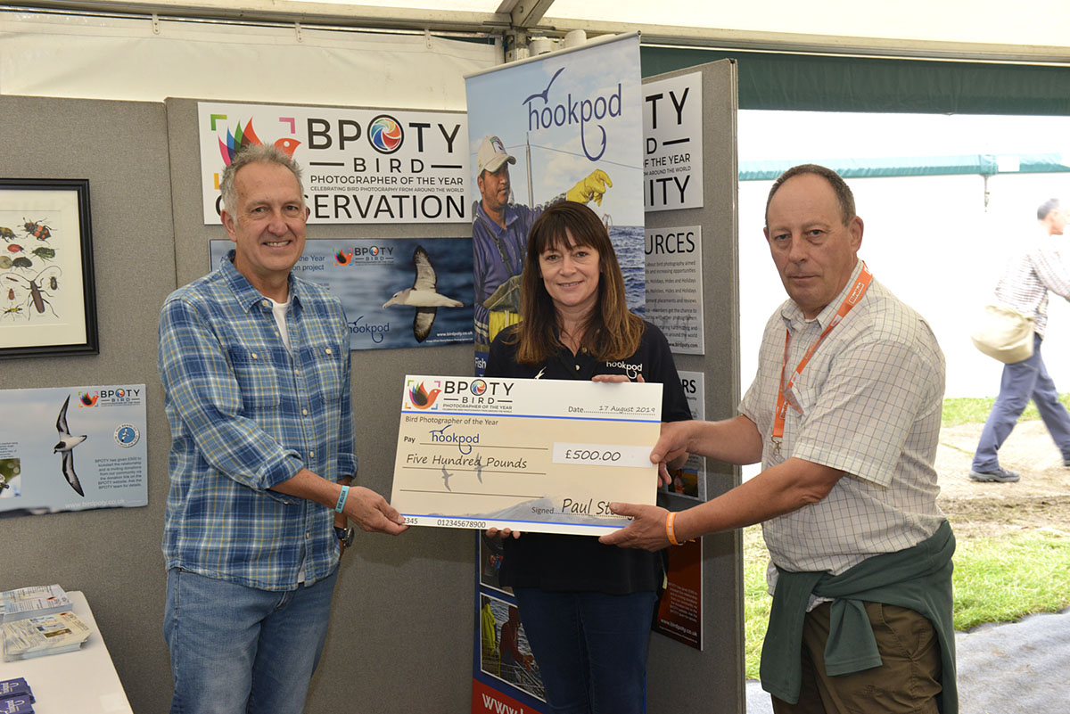 Hookpod CEO Becky Ingham (centre) and Mark Carwardine (left) receiving a cheque for £500 from BPOTY director Paul Sterry (right) at this year's Birdfair. Photo ©Rob Read.
