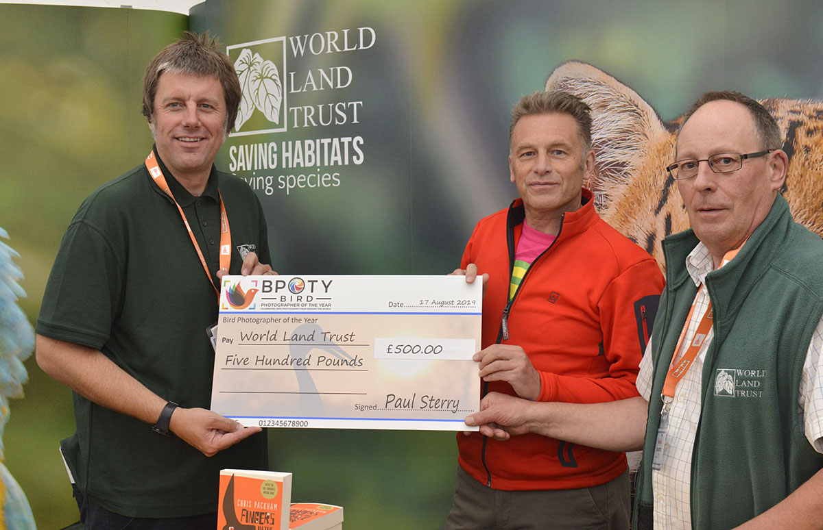 Dan Bradbury Director of Communications and Development of World Land Trust (left) receives a donation from BPOTY judge Chris Packham (centre) and BPOTY director Paul Sterry (right). Photo ©Rob Read.