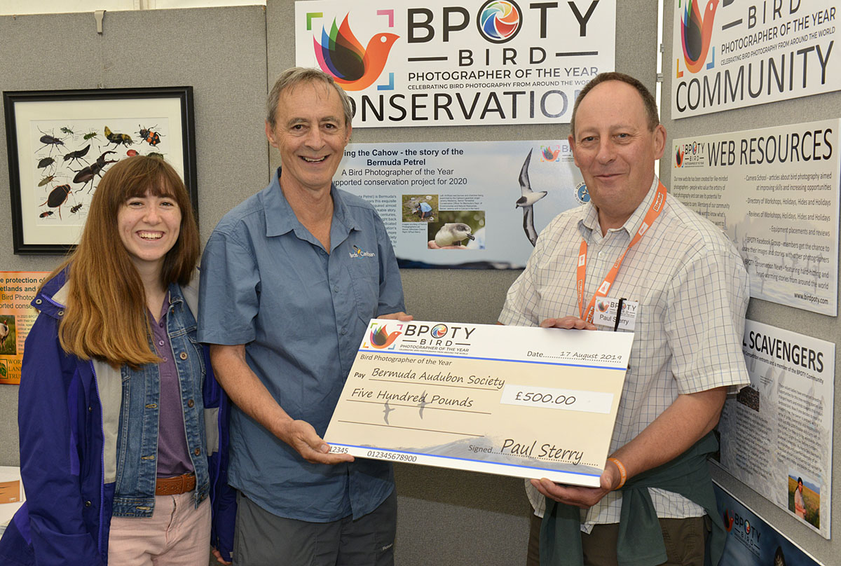 Andrew Dobson (centre) former president of the Bermuda Audubon Society with his daughter Fiona (left) receive a donation from BPOTY director Paul Sterry (right). Photo ©Rob Read.